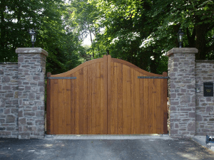 wooden driveway gate with trees in background