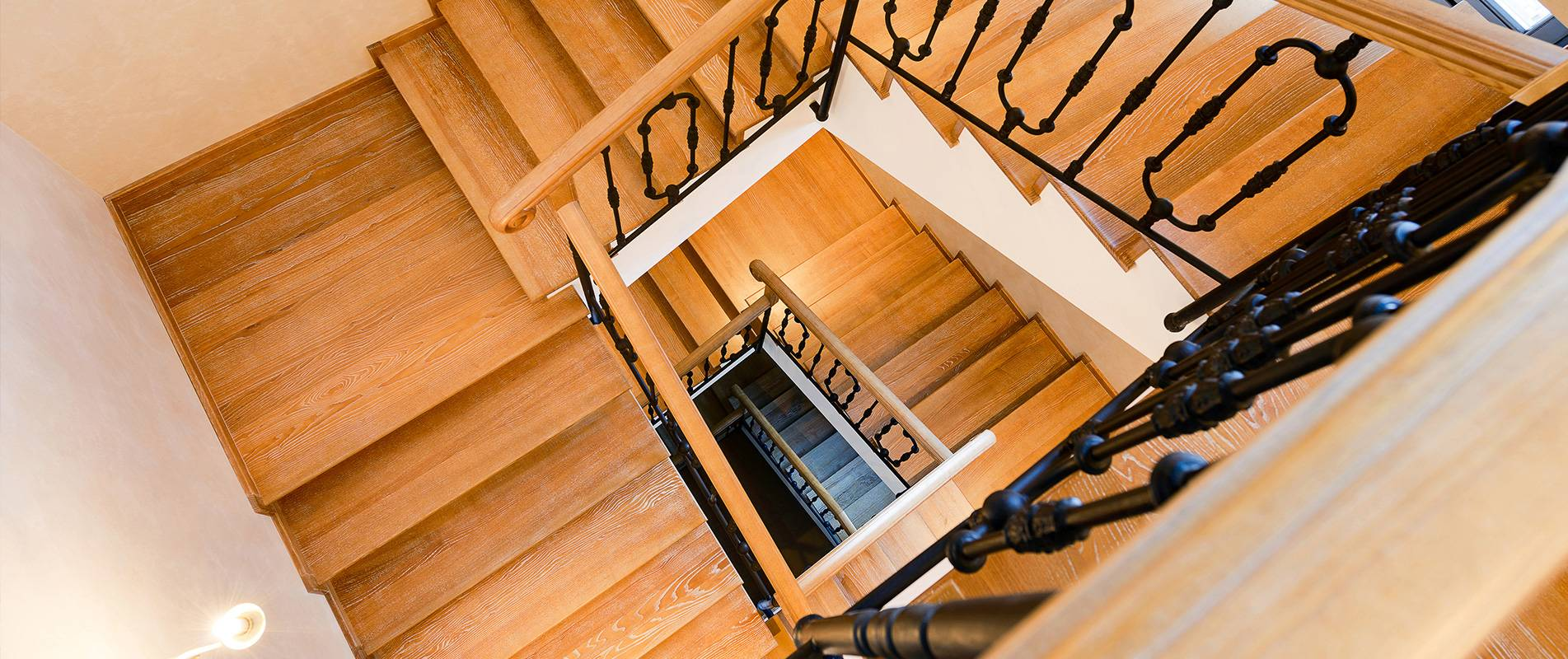 wooden spiral staircase with black ballestrading