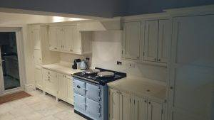 white wooden kitchen cabinets with blue aga