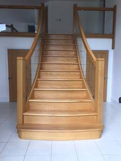 wooden staircase with glass panels