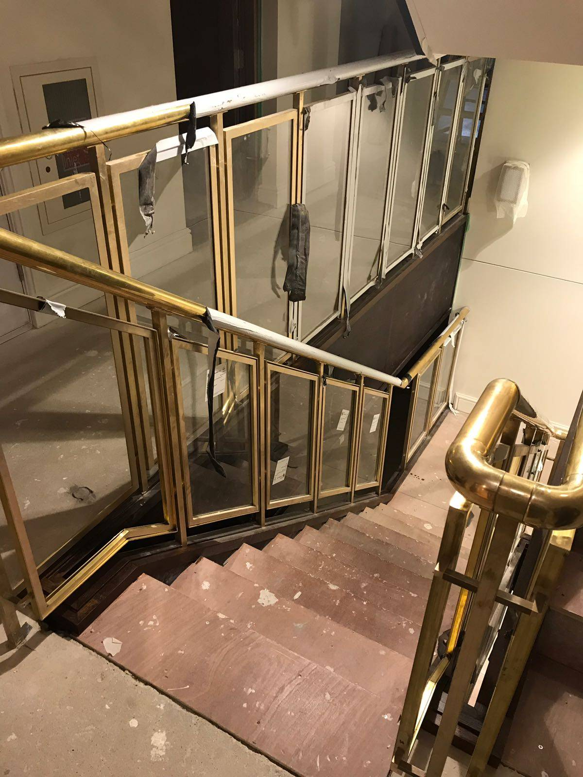 new wooden staircase, with brass stair rail and glass balustrade panels